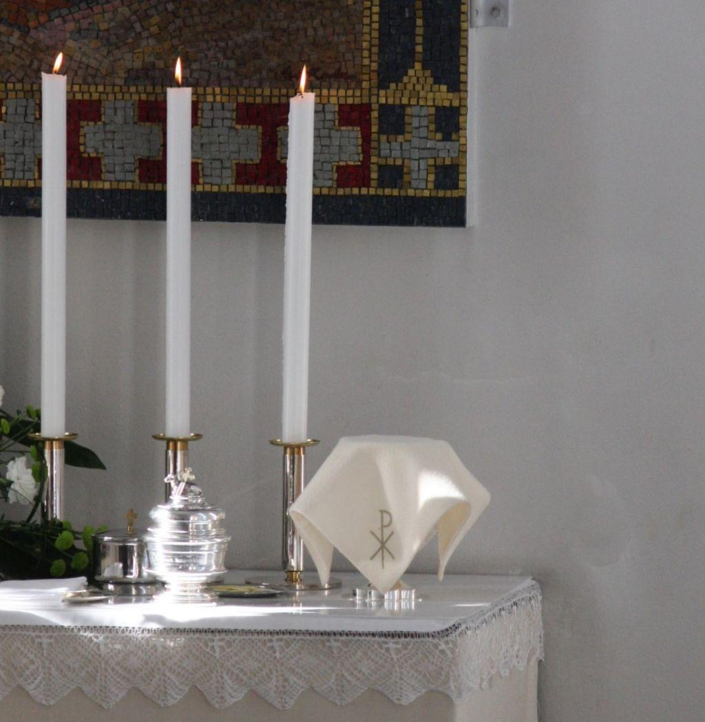 Ehtoollisaineet ja kynttilät alttarilla