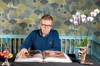 Pastori Ari Luomajoki lukee pöydän ääressä taidehistoriallista teosta.